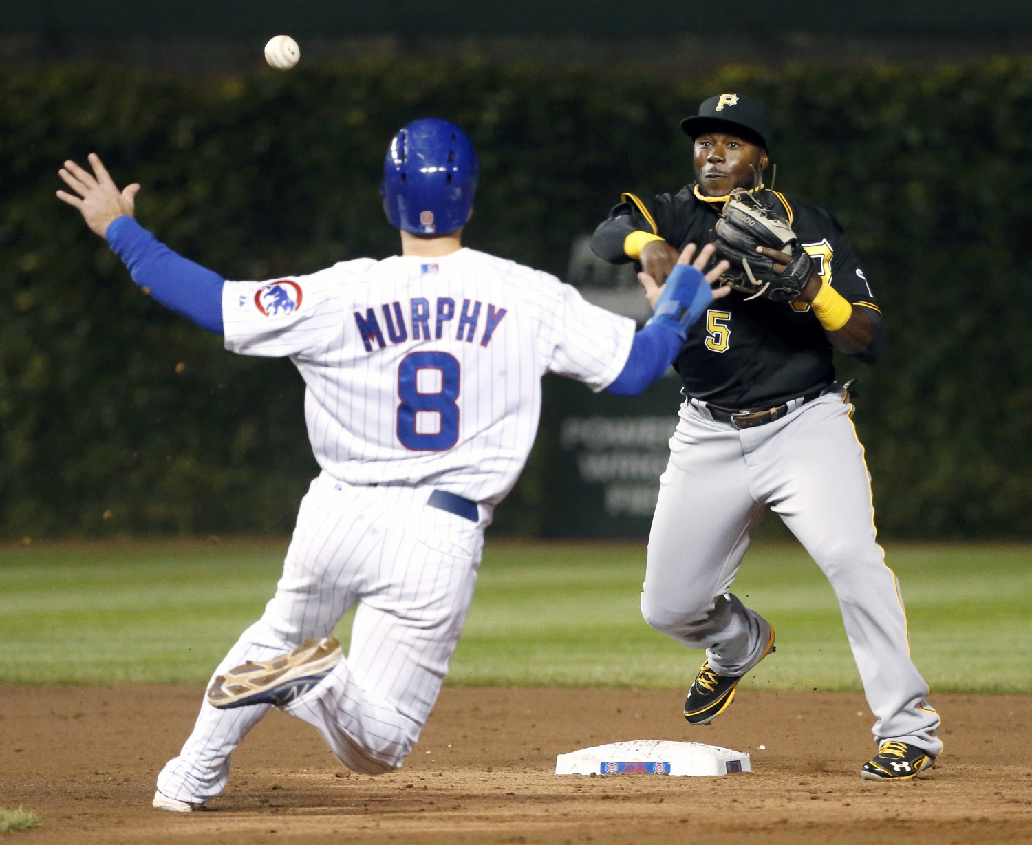 Pittsburgh Pirates second baseman Josh Harrison (5) turns the double play forcing Chicago Cubs' Donnie Murphy (8) at second and getting Brian Bogusevic at first during the second inning of a baseball game Tuesday, Sept. 24, 2013, in Chicago. (AP Photo/Charles Rex Arbogast)