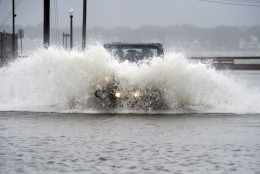 A Jeep drives on a flooded street at high-tide in downtown Ocean City, Md., Saturday, Oct. 3, 2015. Rain pummeling parts of the East Coast showed little sign of slackening Saturday, with record-setting precipitation prolonging the soppy misery that has been eased only by news that powerful Hurricane Joaquin will not hit the U.S. (AP Photo/Cliff Owen)