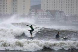 Surfers catch waves in the Absecon Inlet off the shore of Brigantine, N.J. along the Atlantic City skyline, Saturday, Oct. 3, 2015, as a storm brought heavy winds and rain to the Jersey shore communities. (Lori M. Nichols/NJ.com via AP)