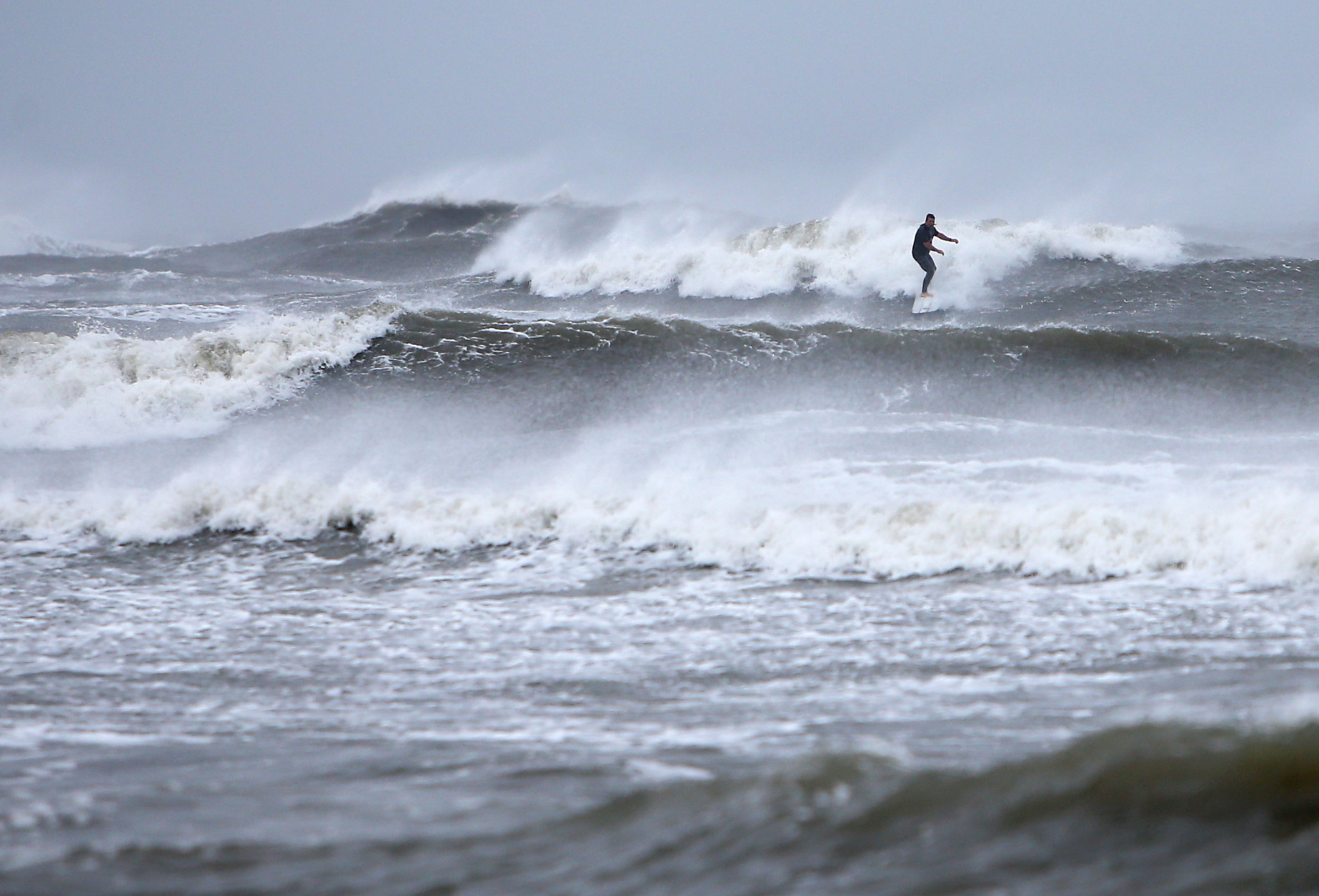 A surfer catches a wave in the Absecon Inlet off the shore of Brigantine, N.J., Saturday, Oct. 3, 2015, as a strom brought heavy winds and rain to the Jersey shore communities. (Lori M. Nichols/NJ.com via AP)