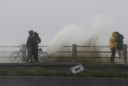 People shield themselves as a wave crashes against a walkway in Charleston, S.C., Saturday, Oct. 3, 2015.  Rain pummeling parts of the East Coast showed little sign of slackening Saturday, with record-setting precipitation prolonging the soppy misery that has been eased only by news that powerful Hurricane Joaquin will not hit the U.S.  (AP Photo/Chuck Burton)