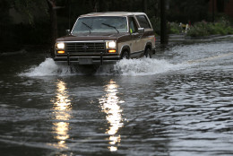 A motorist drives his truck through a flooded street in Charleston, S.C., Sunday, Oct. 4, 2015. President Barack Obama declared a state of emergency in South Carolina and ordered federal aid to bolster state and local efforts as flood warnings remained in effect for many parts of the East Coast through Sunday. (AP Photo/Chuck Burton)