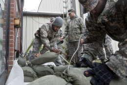 Airmen and volunteers place sandbags outside of a building at Langley Air Force Base Thursday afternoon, Oct. 1, 2015, as heavy rain falls in Hampton, Va. The base  will be closed to all non-mission essential personnel beginning Friday morning. The base's leadership made the decision based on projected tidal surges and potential flooding from Hurricane Joaquin. (Kaitlin McKeown/The Daily Press via AP) MANDATORY CREDIT