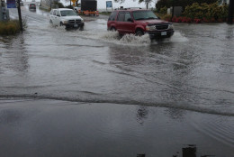 Cars drive through a flooded intersection during high tide on Chincoteague Island, Va., on Friday, Oct. 2, 2015.  Virginia State Police say they've responded to dozens of vehicle crashes throughout the state as heavy rains cause problems for motorists.  (AP Photo/David Dishneau)