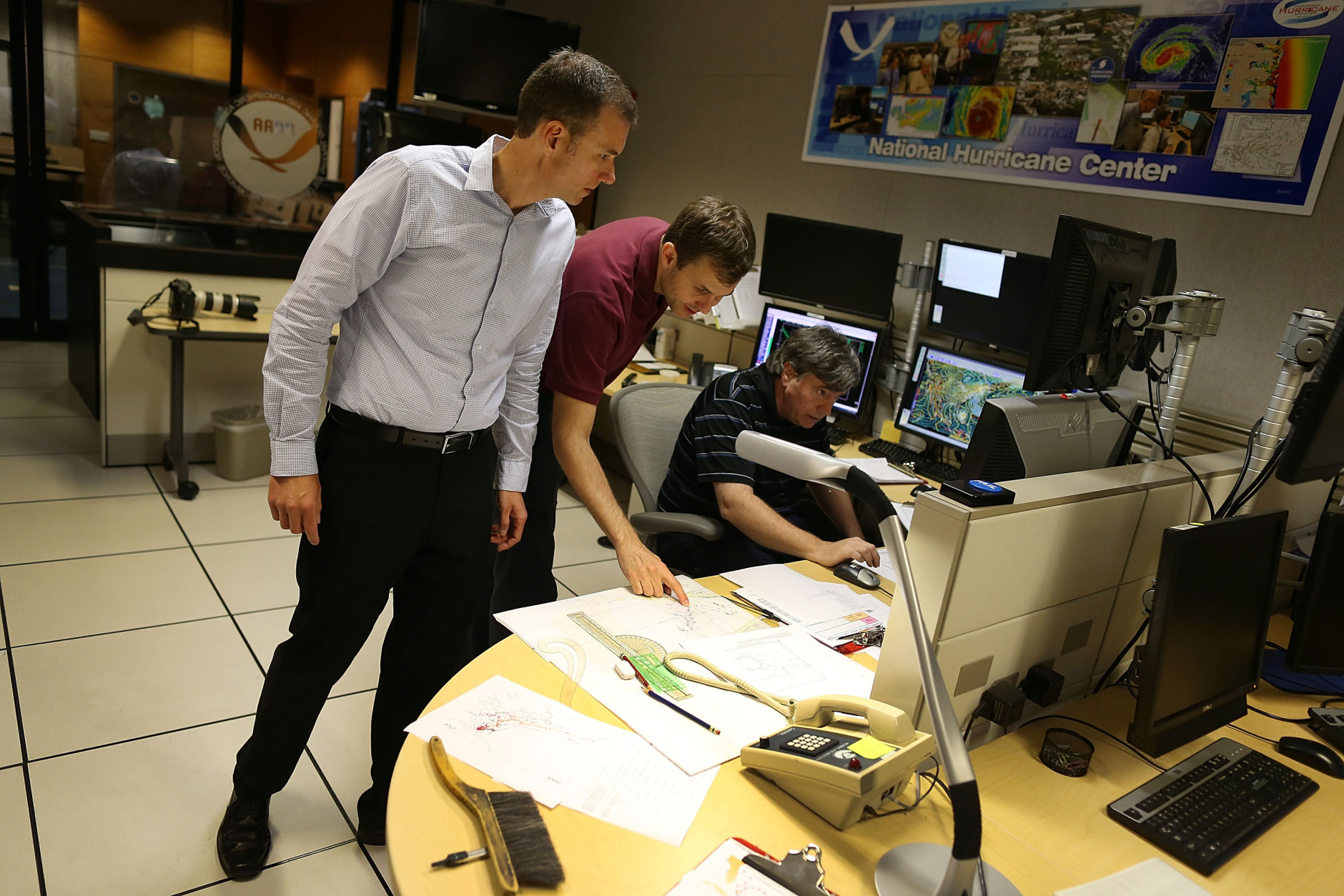 MIAMI, FL - OCTOBER 01:  Jamie Rhome, Storm Surge Specialist, Eric Blake, Hurricane Specialist, and Jack Beven, Senior Hurricane Specialist, (L-R) work in the National Hurricane Center as they track the path of Hurricane Joaquin, a Category 3 storm with maximum sustained winds of 125 mph, as it passes over parts of the Bahamas on October 1, 2015 in Miami, Florida. The forecasters are still trying to determine if the hurricane will turn to the north and northwest, which might affect the U.S. East Coast.  (Photo by Joe Raedle/Getty Images)