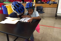 Two CW Harris Elementary School students check out some paperwork before the big event. (WTOP/Kate Ryan)