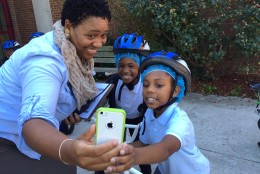 CW Harris Elementary School principal Heather Hairston takes a selfie with students before they ride. (WTOP/Kate Ryan)