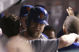 New York Mets' Lucas Duda is congratulated in the dugout after hitting a three-run home run during the first inning of Game 4 of the National League baseball championship series against the Chicago Cubs Wednesday, Oct. 21, 2015, in Chicago. (AP Photo/David J. Phillip)
