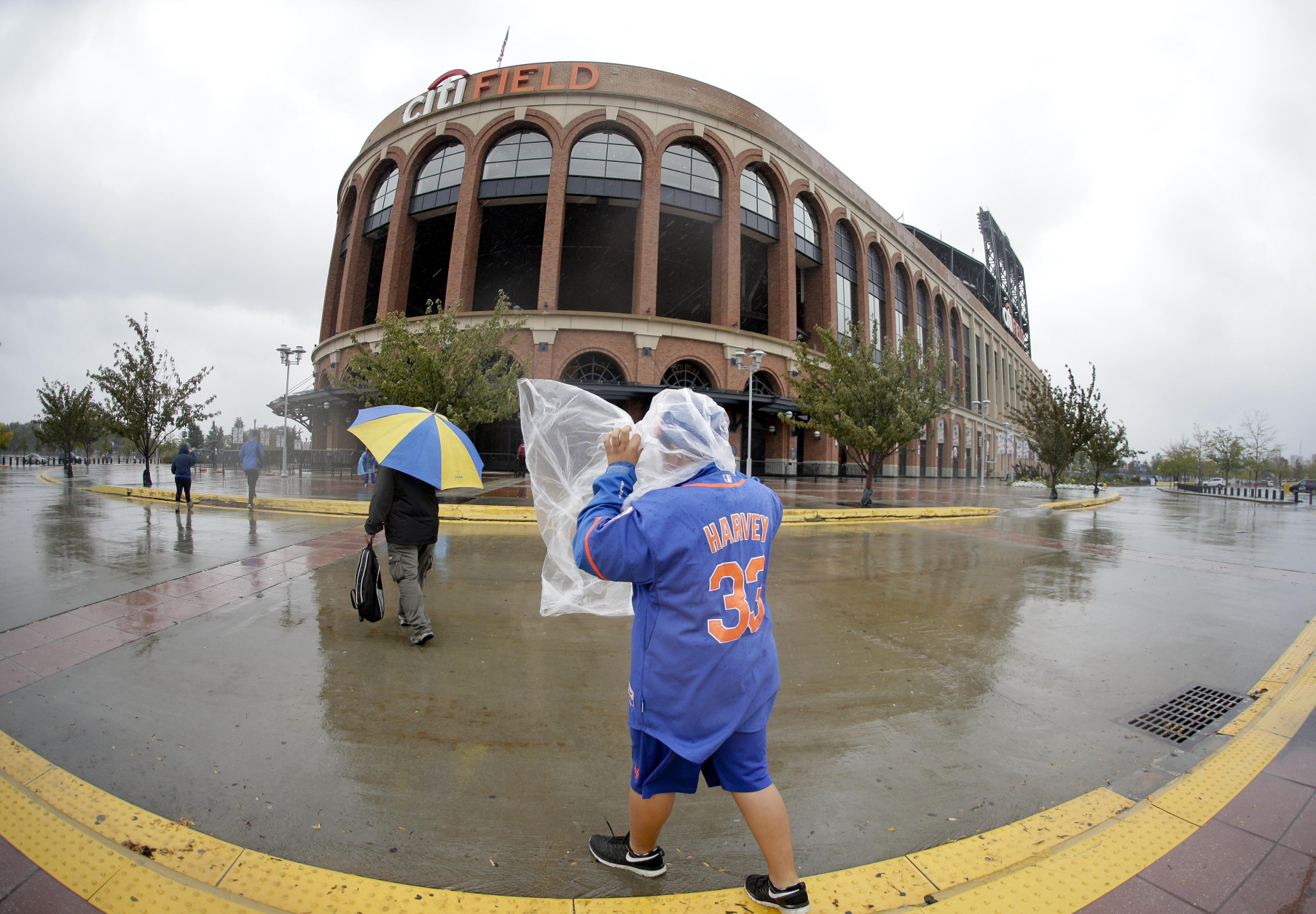 A baseball fan walks around Citi Field after the baseball game between the Washington Nationals and New York Mets was postponed because of rain, Friday, Oct. 2, 2015, in New York. The game will be played on Saturday as a double header. (AP Photo/Julie Jacobson)