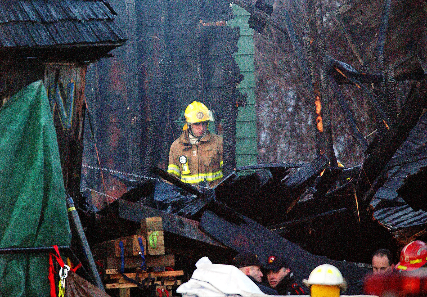 FILE - In this Feb. 21, 2003 file photo, a firefighter inspects the charred interior of the Station nightclub after a fatal fire at the club in West Warwick, R.I. A deadly nightclub fire at the Colectiv club in downtown Bucharest, Romania has claimed some dozens of lives and left at least over a hundred people injured early on Saturday, Oct. 31, 2015. Survivors and families of victims of a deadly nightclub blaze in Rhode Island over a decade ago say the tragedy in Bucharest, Romania, is sadly and eerily similar. (AP Photo/Michael Dwyer, File)