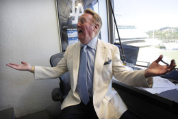 Vin Scully talks to a well-wisher in his booth at Dodger Stadium in Los Angeles, Sunday, Aug. 22, 2010. Scully will return to the broadcast booth to call Los Angeles Dodgers games next year for his 62nd season. The team said Sunday that the 82-year-old Hall-of-Famer will call all home games and road games against National League West opponents. (AP Photo/Jae C. Hong)