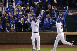 Kansas City Royals' Alcides Escobar, right, celebrates his on a inside-the-park home run with Ben Zobrist during the first inning of Game 1 of the Major League Baseball World Series against the New York Mets Tuesday, Oct. 27, 2015, in Kansas City, Mo. (AP Photo/Charlie Riedel)