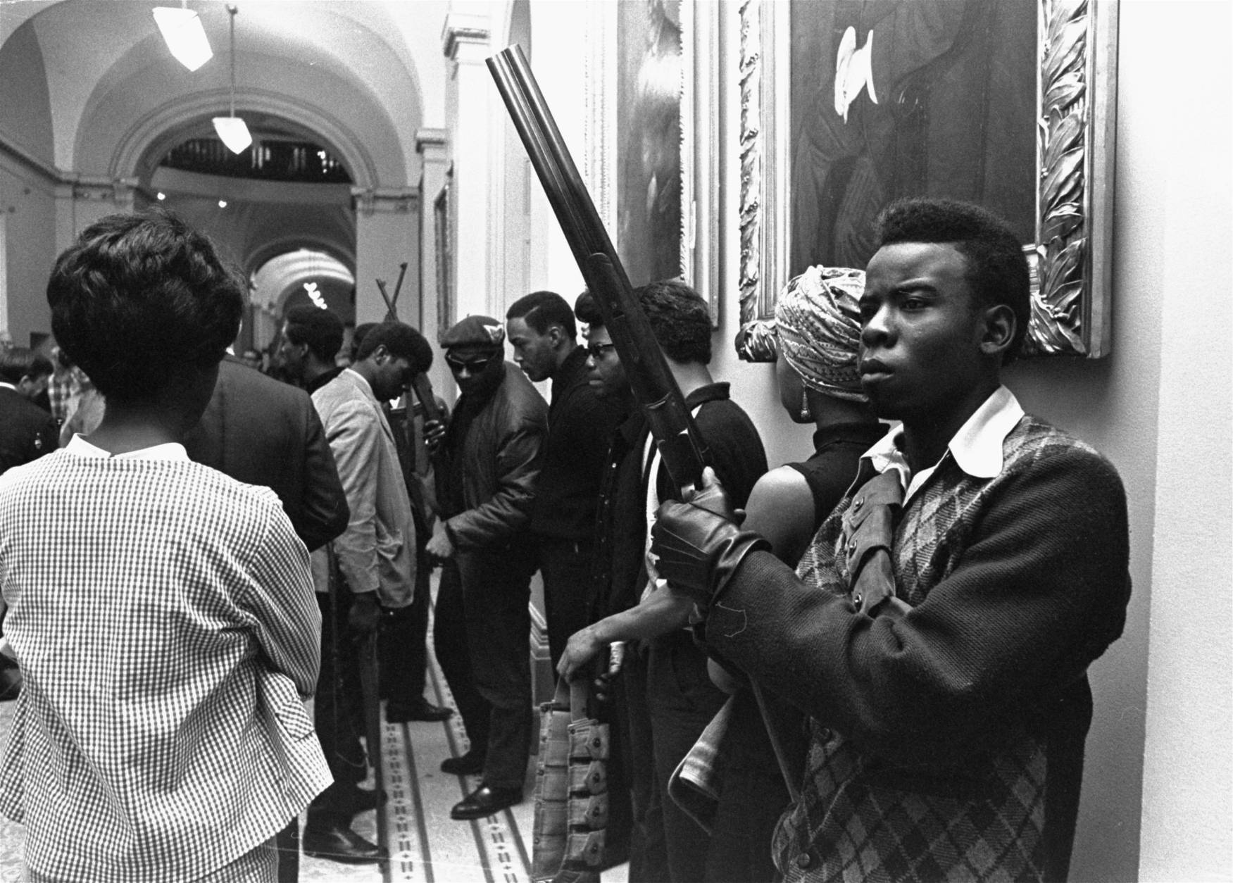 Armed members of the Black Panthers Party stand in the corridor of the Capitol in Sacramento today, May 2, 1967.  They were protesting  a bill before an Assembly committee restricting the carrying of arms in public.  (AP Photo/Walt Zeboski)