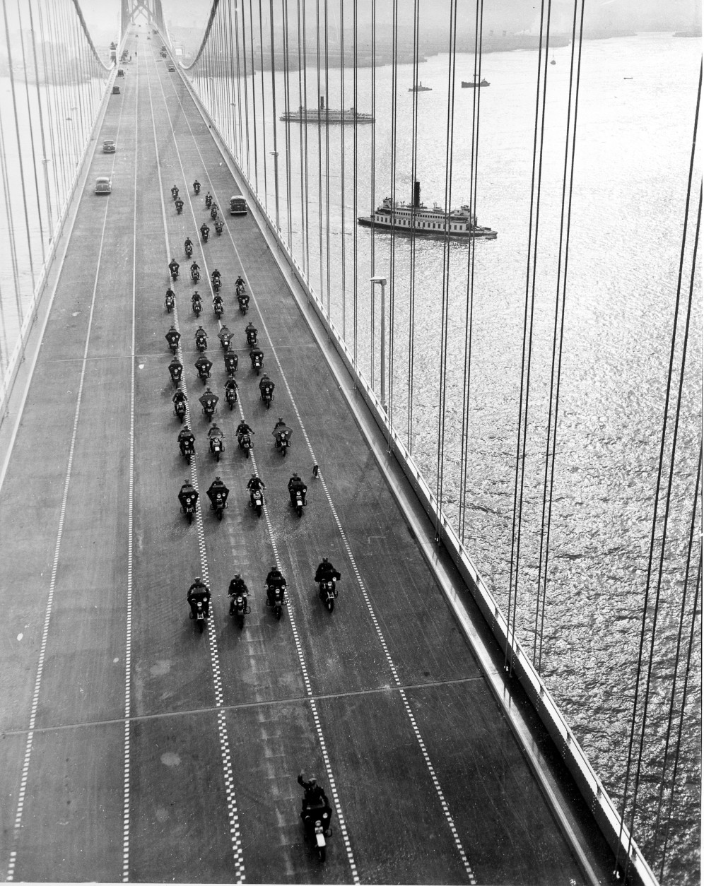 In this Nov. 12, 1936 photo, State Highway policemen cross the western span of the San Francisco-Oakland Bay Bridge during its opening in San Francisco.  The project cost  $77.6 million. The bridge has been closed indefinitely after a rod installed during last month's emergency repairs snapped, Tuesday, Oct. 27, 2009, causing a traffic nightmare for the 280,000 motorists who cross the landmark span every day. (AP Photo)