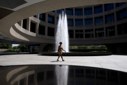 A woman walks past the fountain in the courtyard of the Hirshhorn Museum and Sculpture Garden in Washington, Thursday, Aug. 13, 2015. (AP Photo/Carolyn Kaster)