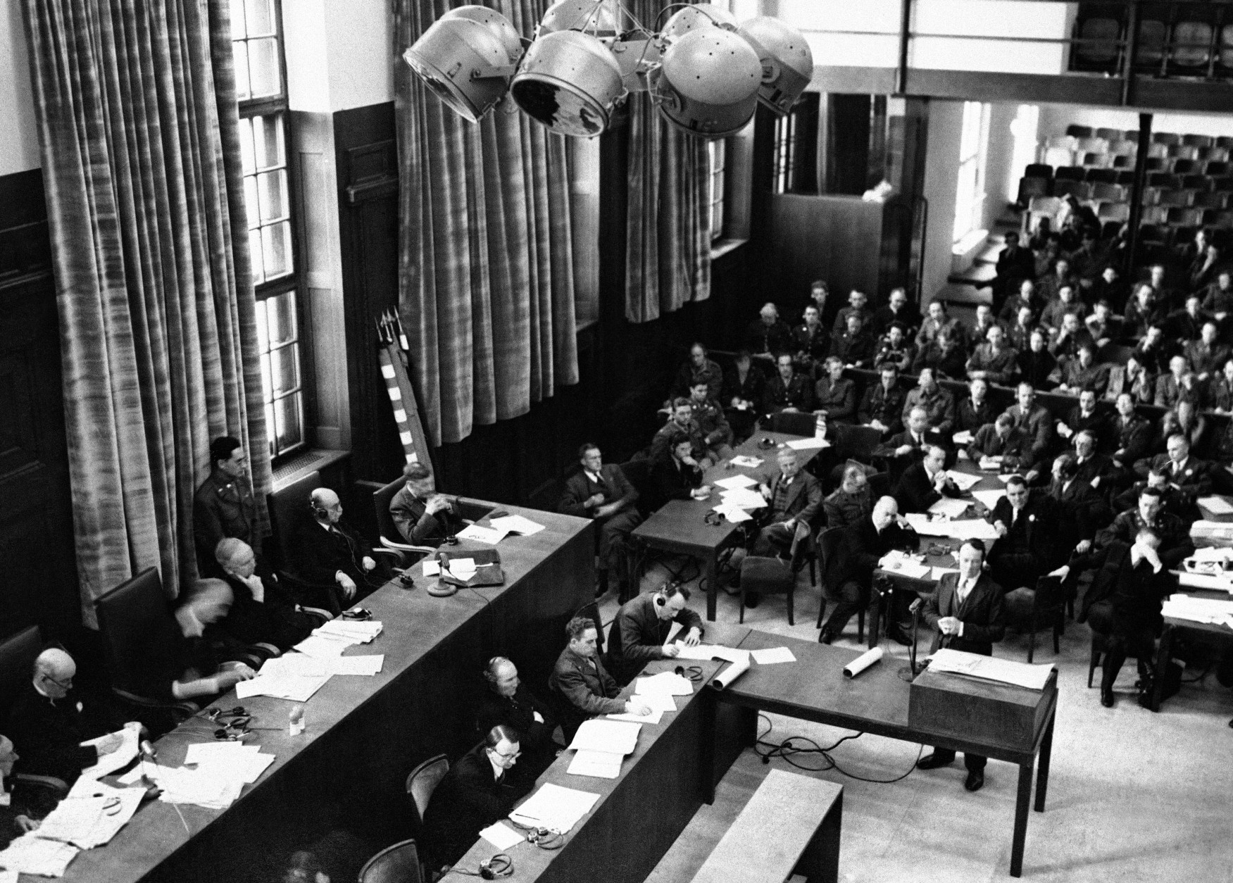 The British Attorney General Sir Hartley Shawcross speaking at the War Crimes Tribunal at Nuremberg, on Nov. 15, 1945, opposed a possible postponement of the Nuremberg trials. A medical report had been read that Gustav Krupp the munitions magnate was dying and was unlikely to face trial. The British Attorney General Sir Hartley Shawcross, bottom right, is seen addressing the court at Nuremberg. (AP Photo)