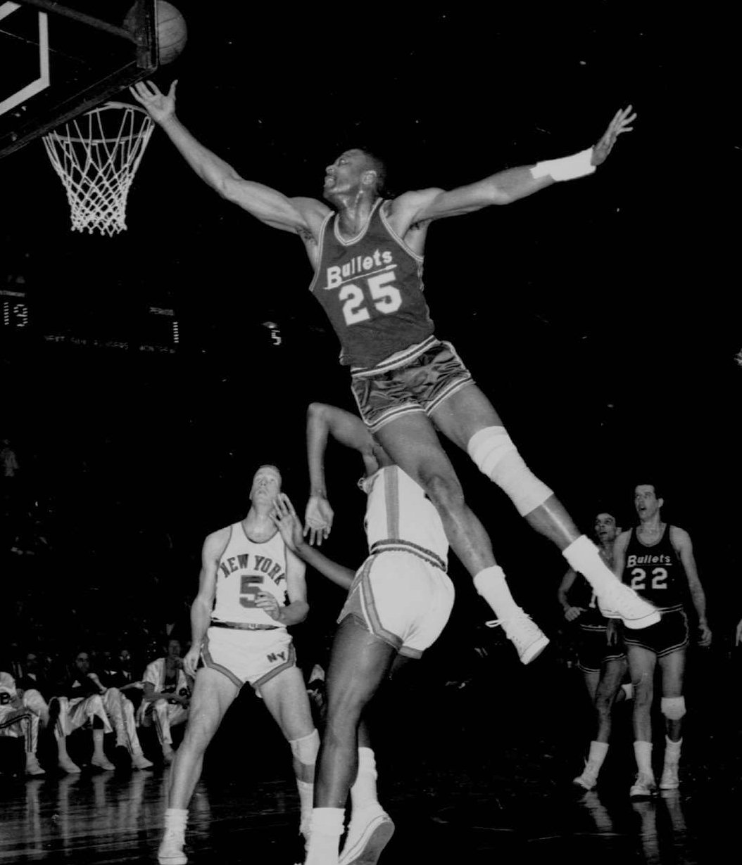 Baltimore Bullets Gus Johnson goes to the basket, landing on New York Knicks Dick Barnett, at New York's Madison Square Garden, Feb. 1, 1966. At lower left is Knicks' Dick Van Arsdale. Johnson was renominated Tuesday Nov. 5, 1996 for the Basketball Hall of Fame. (AP Photo/File)
