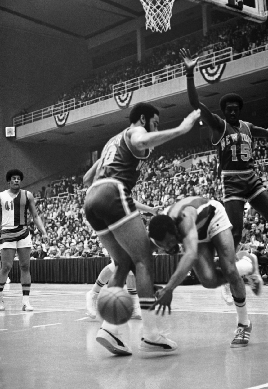 Baltimore Bullet Archie Clark trips on drive toward basket in first period action on Tuesday, April 4, 1972 in Baltimore, in the third playoff game between the Bullets and the New York Knicks. Clark lost the ball and bumped into Walt Frazier, left, after his approach to the basket was blocked by New York?s Earl Monroe. The National Basketball Association series was tied 1-1 going into Tuesday?s action. (AP Photo)