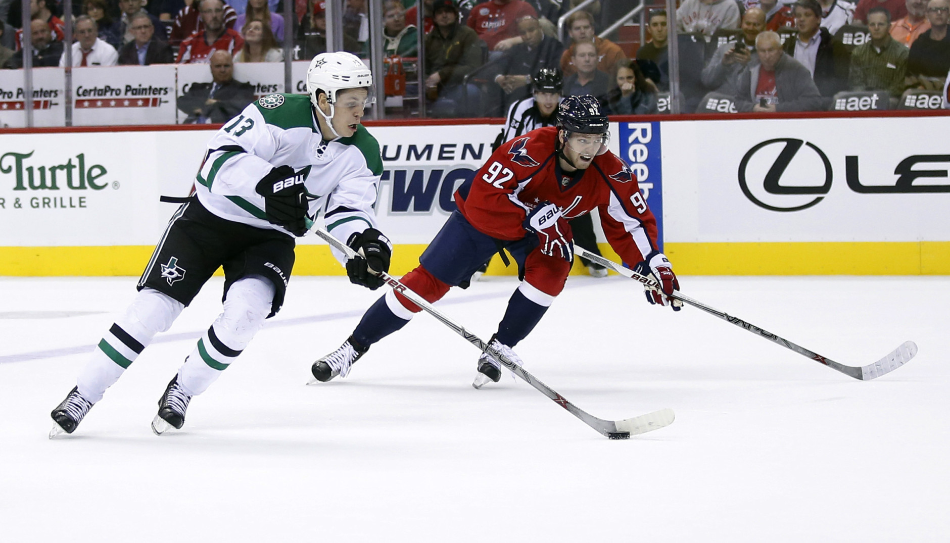 Dallas Stars center Mattias Janmark (13), from Sweden, skates with the puck as Washington Capitals center Evgeny Kuznetsov (92), from Russia, defends during the second period of an NHL hockey game, Thursday, Nov. 19, 2015, in Washington. (AP Photo/Alex Brandon)