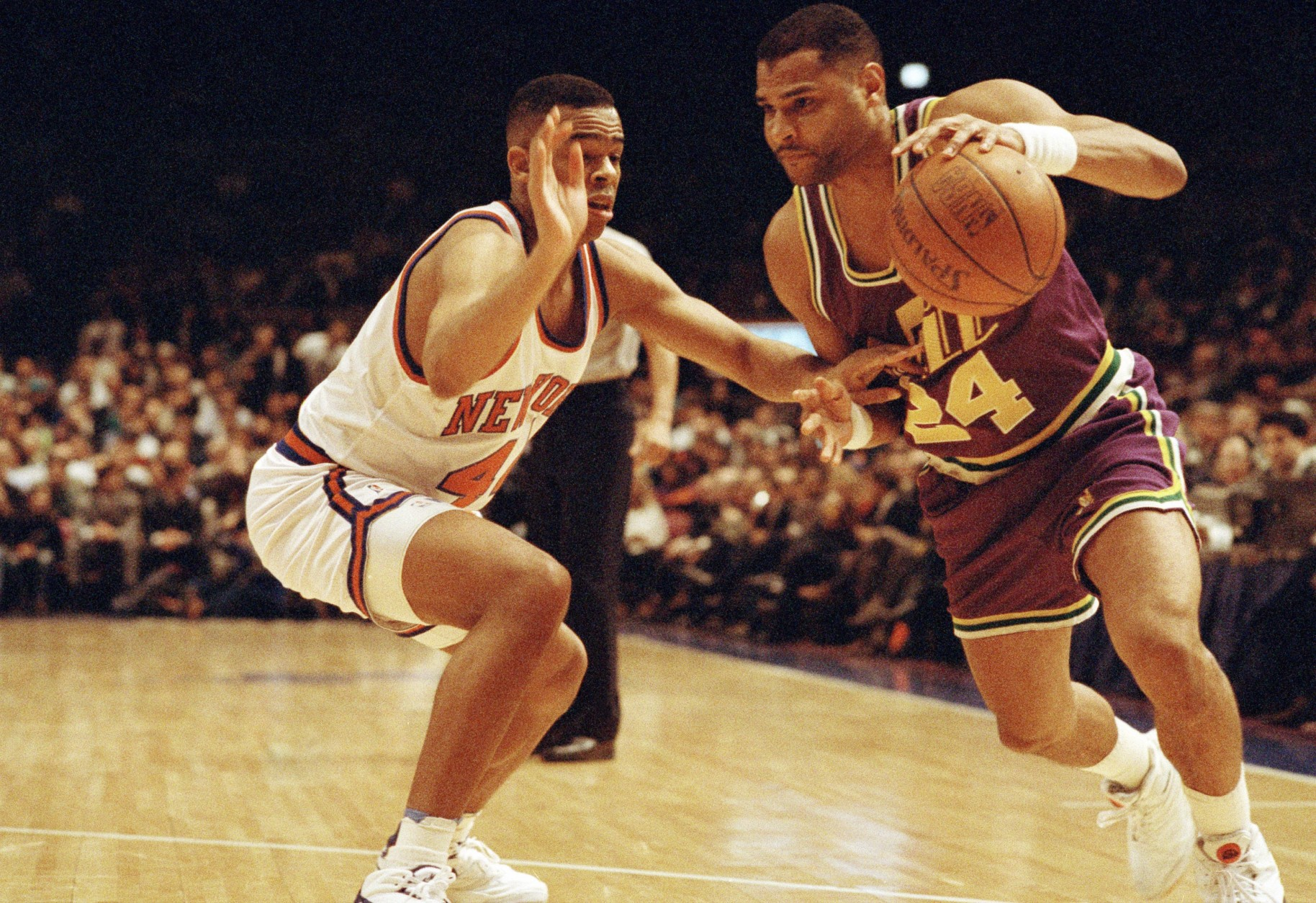 Utah Jazz player Jeff Malone, right , drives around New York Knicks player Hubert Davis during first quarter NBA action at Madison Square Garden in New York March 4, 1993. (AP Photo/Kevin Larkin)