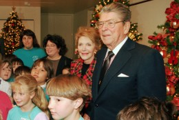 """Former President Ronald Reagan and his wife Nancy pose for pictures during a tour of the """"Christmas Around the World"""" exhibit at the Ronald Reagan Presidential Library and Museum Tuesday, Nov. 22, 1994, in Simi Valley, Calif.  The event marked the former President's first public appearance since the Nov. 5, 1994, public announcement that he has been diagnosed with Alzheimer's disease.  The disease seems to have silenced Reagan, who cherished the moments he spent spinning yarns about Hollywood andthe White House.  (AP Photo/Mark J. Terrill)"""