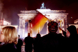 A young man waves a German flag in front of the Brandenburg gate during a party marking the tenth anniversary of the the fall of the Berlin Wall, in Berlin,Tuesday, November 9, 1999. (AP Photo/Jockel Finck)