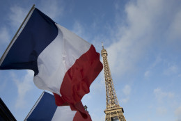 FILE - In this Sunday Nov. 15, 2015 file photo, French flags fly in front of the closed Eiffel Tower on the first of three days of national mourning in Paris. Paris' main flag-maker has recorded a 500 percent increase in Tricolor sales since the Nov 13 attacks, claimed by the Islamic State group. Until now, flags were generally known to fly in numbers around Paris but on official buildings or random flag poles _ not on private residences. (AP Photo/Peter Dejong, File)