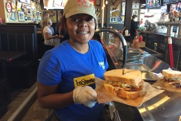 A server happily shows off a famous Primanti Bros. sandwich about to be delivered to a hungry customer. (WTOP/Michelle Basch)