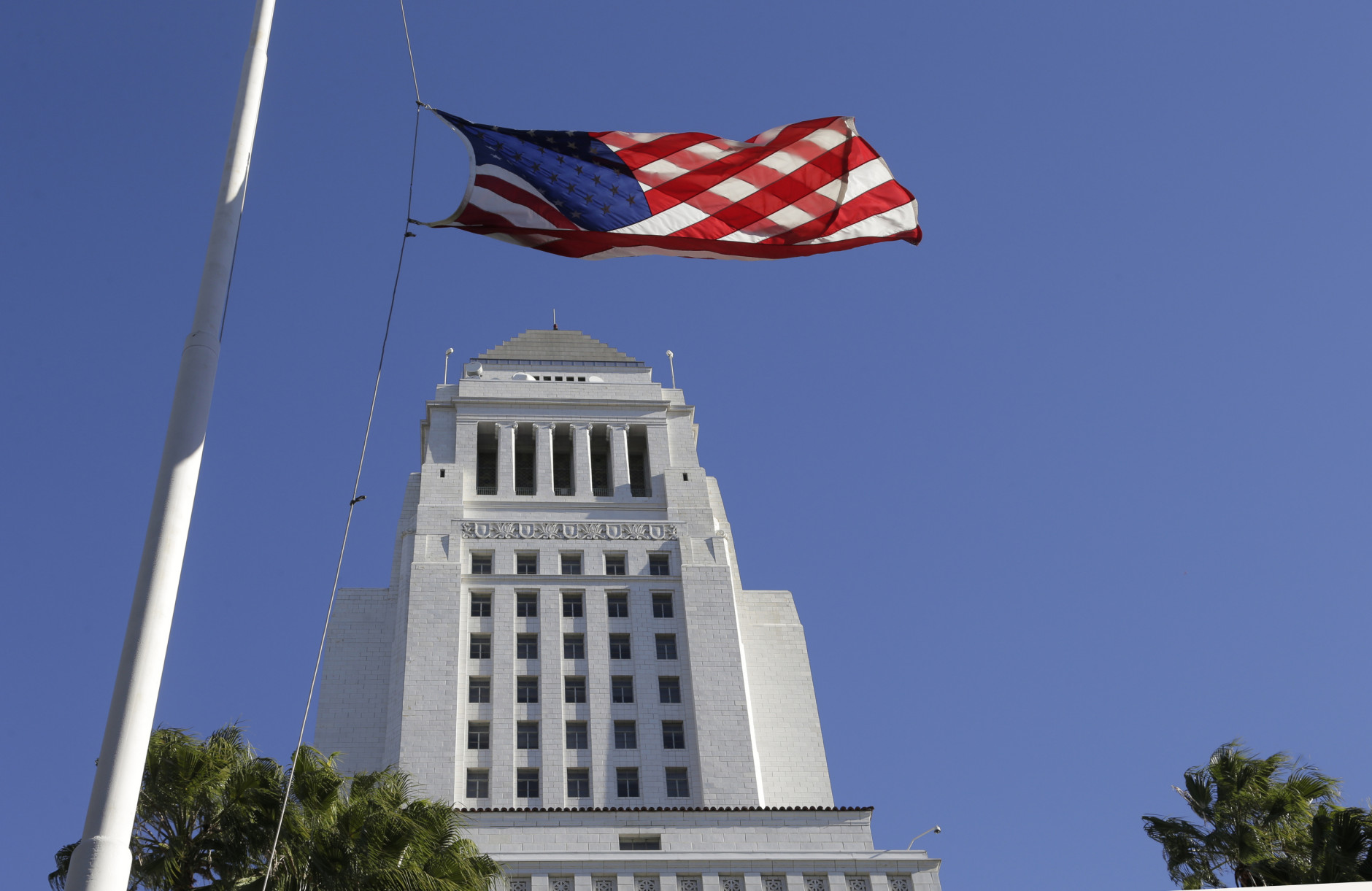 An American flag flies half-staff in a strong wind at Los Angeles City Hall on Monday, Nov. 16, 2015. The winds followed a front that moved through California during the weekend, dropping rain and snow while lowering temperatures.  Flags fly at half-staff in Los Angeles in honor of victims of terrorist attacks in Paris. (AP Photo/Nick Ut)