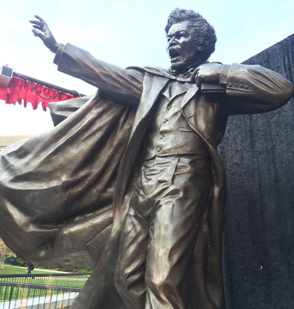 The bronze statue of Frederick Douglass portrays a youthful Douglass, 15 years before the start of the Civil War, his cape flowing from his shoulders, right arm thrust forward, his mouth wide-open in exhortation. (WTOP/Dick Uliano)