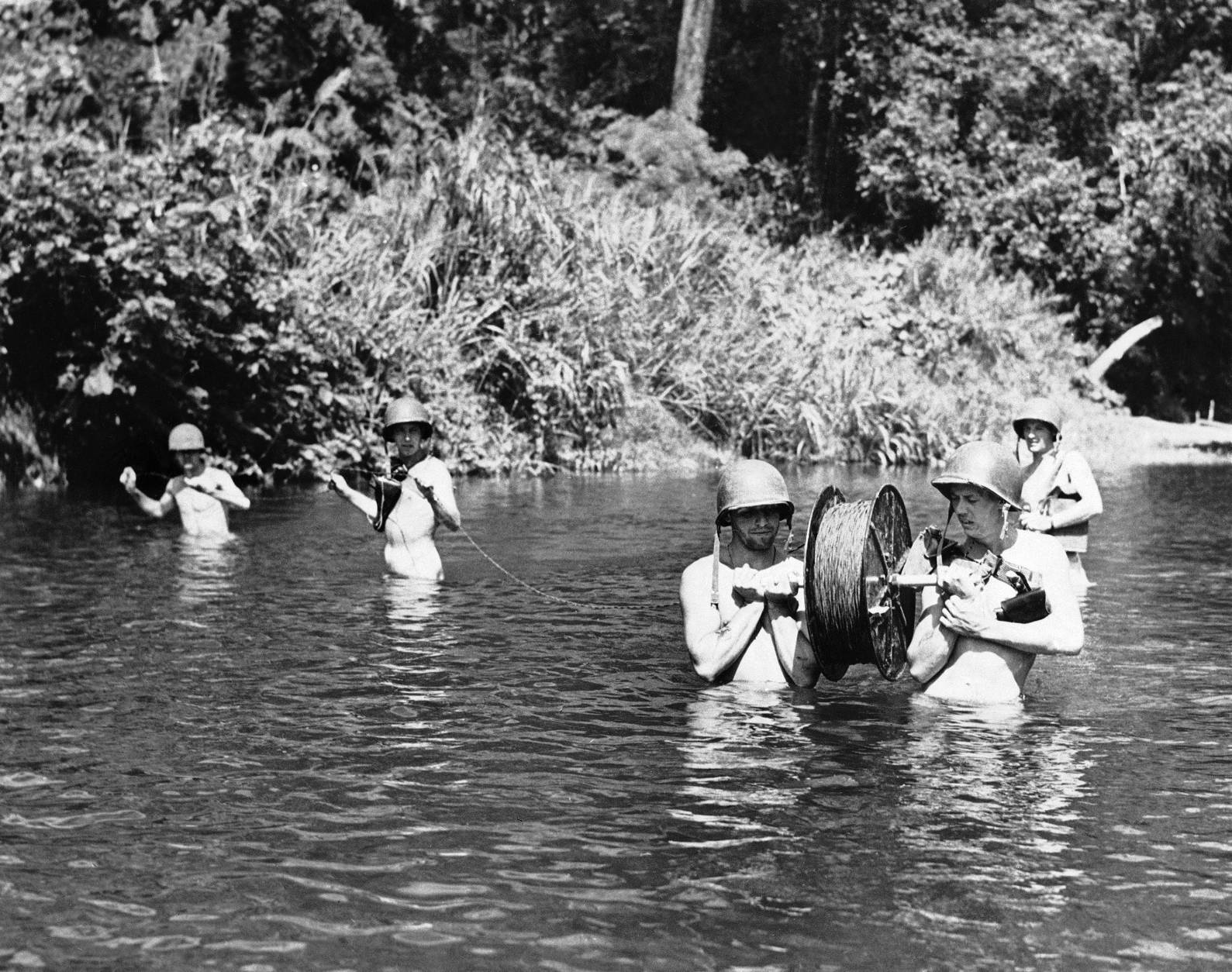Crew of U.S. Marines fords a river on Guadalcanal, in the Solomon Islands, to lay a telephone wire on Nov. 12, 1942. They strip down to get the wire across the Longa River to provide speedy military communication. (AP Photo/Pool)