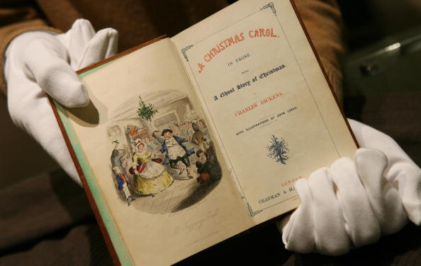 """UNITED KINGDOM - DECEMBER 05:  An employee at Sotheby's holds an 1843 first edition of the classic """"A Christmas Carol"""" by Charles Dickens in London, U.K., Tuesday, December 5, 2006. This and other Christmas books, manuscripts, drawings and related ephemera collected by Jock Elliott, will be auctioned in New York on December 12, and are estimated to sell for $10,000-$15,000 (?5,050 - 7,600)  (Photo by Suzanne Plunkett/Bloomberg via Getty Images)"""
