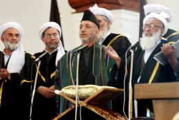 Afghan President Hamid Karzai, center, stands next to Chief Justice Fazl Hadi Shinwari, right, as he takes the oath of office during a ceremony at the Presidential Palace in Kabul Tuesday, Dec. 7, 2004. Karzai was sworn in Tuesday as Afghanistan's first popularly elected president, calling for sustained help from the international community to bolster a young democracy that sill faces the twin threats of terrorism and drugs. (AP Photo/SHAH Marai, POOL)