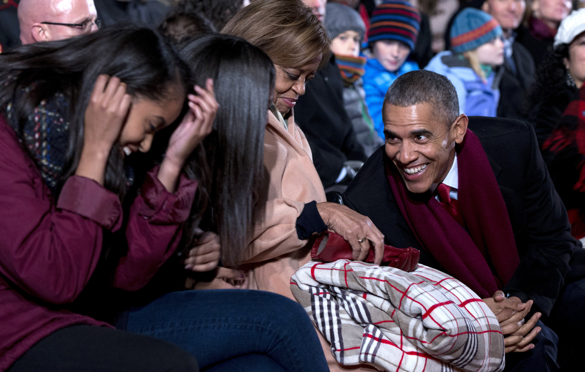 President Barack Obama, leans to talk with his daughters Malia, left, Sasha, second from left, and first lady Michelle Obama's mother Marian Robinson during the National Christmas Tree Lighting ceremony at the Ellipse in Washington, Thursday, Dec. 3, 2015. (AP Photo/Carolyn Kaster)