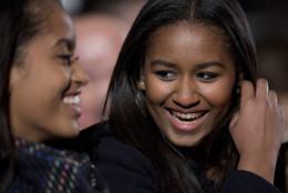 Sasha Obama, right, and Malia Obama, laugh during the National Christmas Tree Lighting ceremony at the Ellipse in Washington, Thursday, Dec. 3, 2015. (AP Photo/Carolyn Kaster)