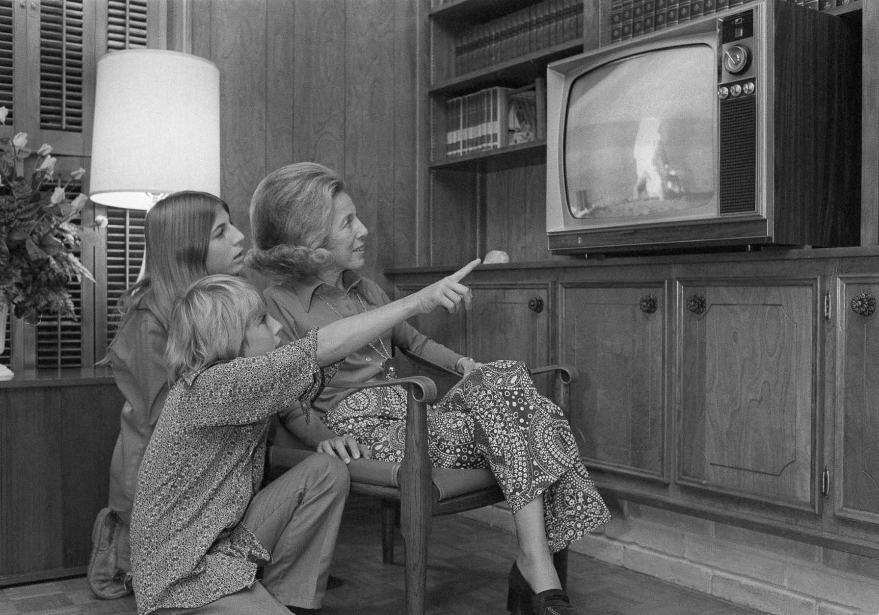 Jon Evans, 11, son of Apollo 17 command module pilot, Ronald E. Evans, points out one of the highlights of the television of the first EVA by moon explorers Eugene A. Cernan and Harrison B. Schmitt, Dec. 11, 1972. Watching with Jon are his mother, Jan Evans , and sistet, Jaime, 13. While the Evans family was watching television in their home near the Manned Spacecraft Center, Houston, Texas, commander Evans was orbiting the moon in the command module. (AP Photo)