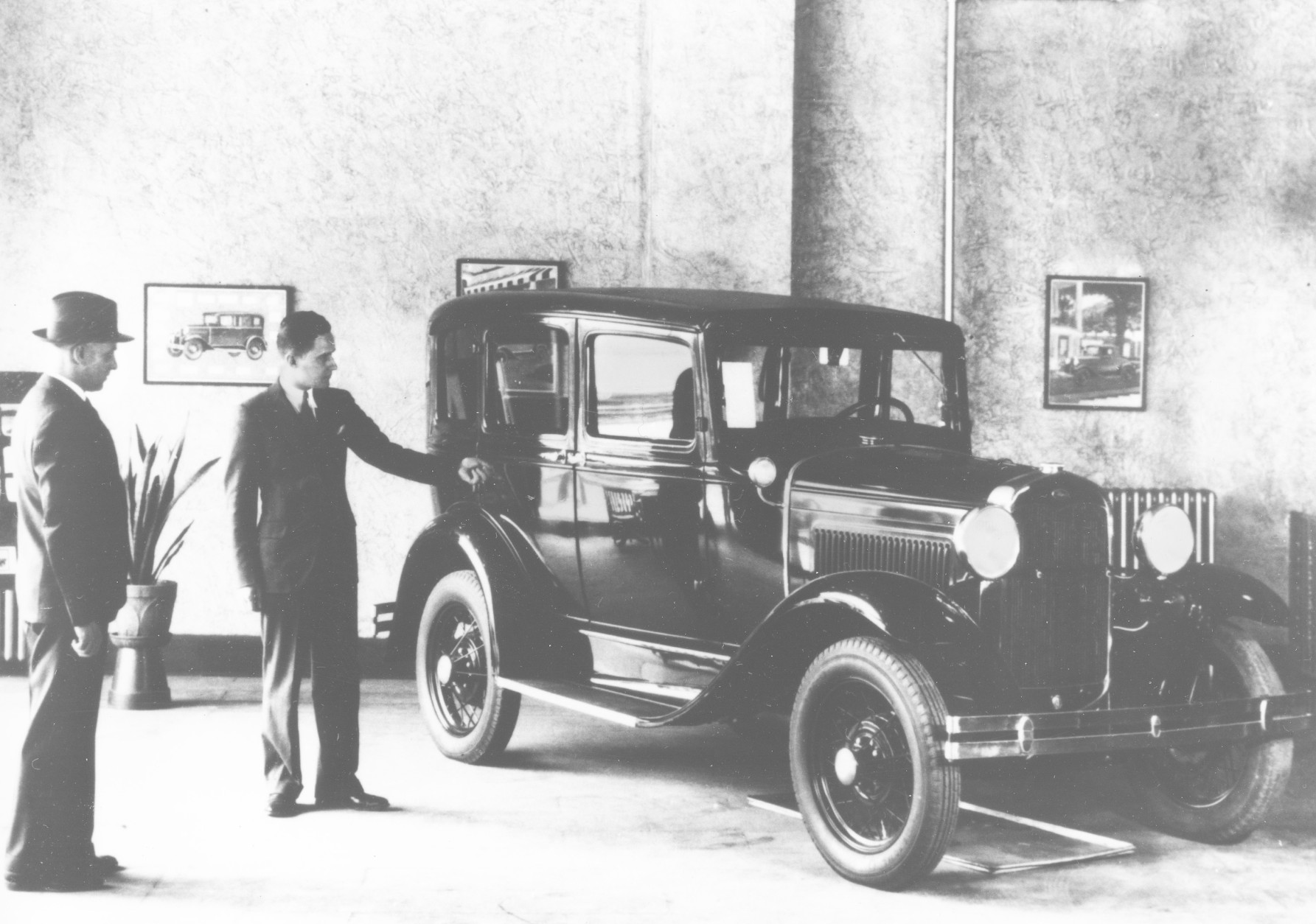 A salesman shows a four-door Ford Model  A to a customer in a showroom in 1931. (AP Photo)