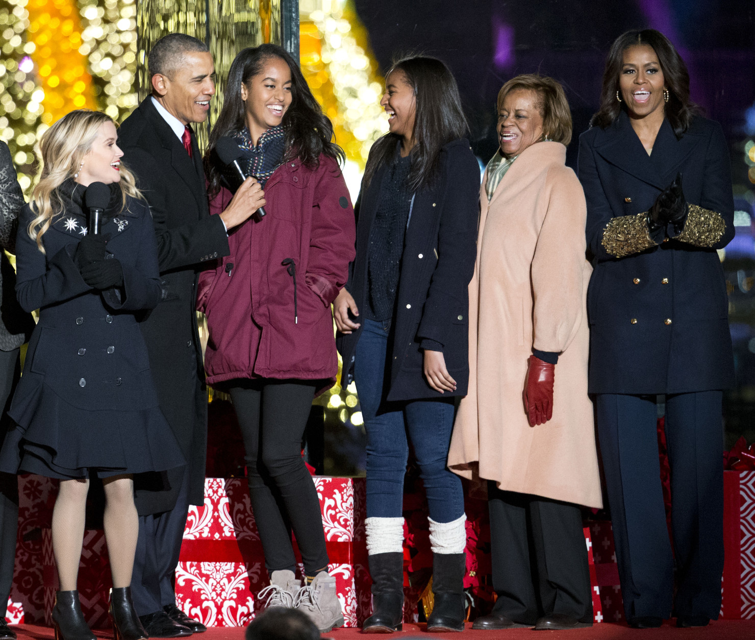 President Barack Obama, left, with daughters Malia and Sasha, mother-in-law Marian Robinson and first lady Michelle Obama sing onstage during the National Christmas Tree Lighting ceremony at the Ellipse in Washington, Thursday, Dec. 3, 2015. Also on stage is actress Reese Witherspoon at left. (AP Photo/Pablo Martinez Monsivais)