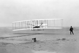 Orville Wright, lying at the controls on the lower wing, pilots  the Wright Flyer on the first powered flight by a heavier-than-air aircraft, Dec. 17, 1903, at Kitty Hawk, N.C. In the moments before going airborne, his brother, Wilbur Wright, watching right, guided and steadied the plane as it accelerated along the starting rail at left. (AP Photo/Library of Congress, John T. Daniels)