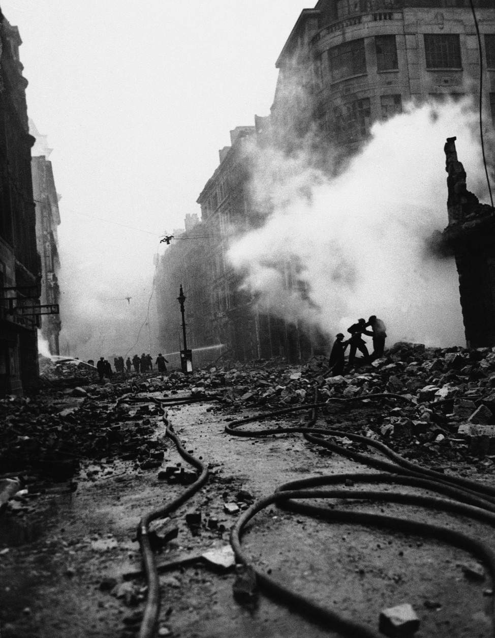 "Newgate Street, in the old section of London, is cluttered with firehoses and debris after the firebombing ""blitz"" raid by the Nazis, Dec. 29, 1940. (AP Photo)"