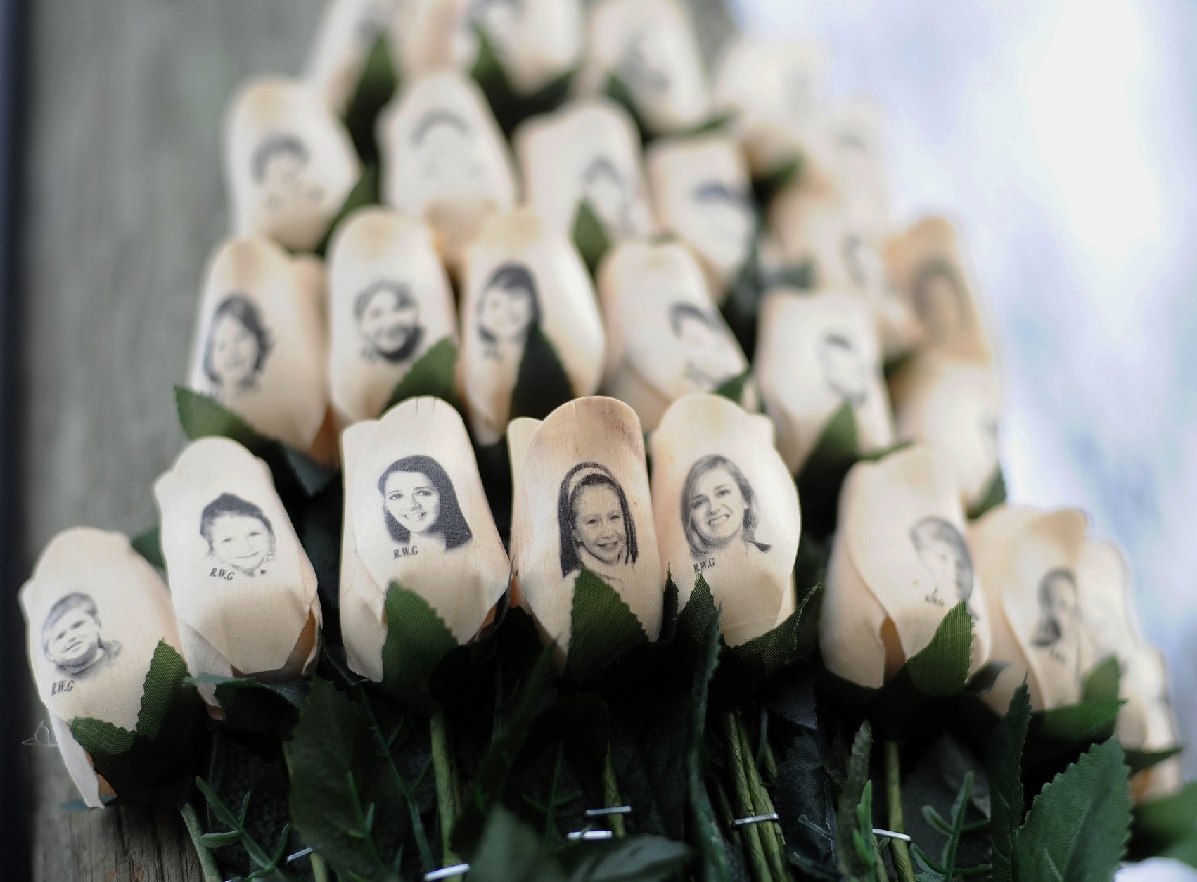 FILE - In this Jan. 14, 2013 file photo, white roses with the faces of victims of the Sandy Hook Elementary School shooting are attached to a telephone pole near the school on the one-month anniversary of the shooting that left 26 dead in Newtown, Conn. The second anniversary of the shooting is Sunday, Dec. 14, 2014 and the town is not holding any public commemoration ceremonies. First Selectman Pat Llodra and school Superintendent Joseph Erardi said the day will be marked through personal reflection and remembrance. (AP Photo/Jessica Hill, File)