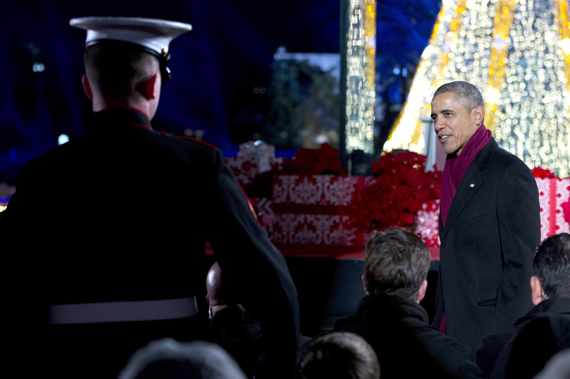 President Barack Obama looks to a member of the military as he walks to his seat during the  National Christmas Tree Lighting ceremony at the Ellipse in Washington, Thursday, Dec. 3, 2015. (AP Photo/Carolyn Kaster)