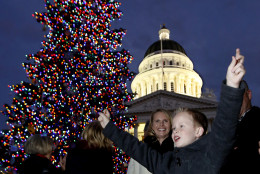 """Jeffery, """"J.J."""" Paris celebrates after lighting the Capitol Christmas tree in Sacramento, Calif., Wednesday, Dec. 2, 2015.  Gov. Jerry Brown had canceled the official lighting ceremony to honor the victims and families of the mass shooting at a San Bernardino facility that includes a center that helps people with developmental disabilities. The 61-foot tall white fir tree was is decorated with more than 10,000 LED lights and 900 hand-crafted ornaments made by children and adults with developmental disabilities who receive services from the state' development centers and nonprofit centers.(AP Photo/Rich Pedroncelli)"""