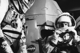 Gemini 7 pilots, Frank Borman, left, and James Lovell, close their pressure suits hoods as they prepare for a practice session in the Gemini mission simulator on Nov. 30, 1965 in Cape Kennedy, Florida. Borman and Lovell will be boosted into orbit by a Titan II rocket on a flight expected to last 14 days starting on December 4. (AP Photo)