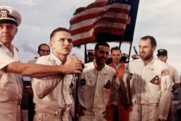 Apollo 8 Spacecraft commander Frank Borman addresses the crew of the USS Yorktown while Apollo 8 astronauts Bill Anders, center, and Jim Lovell, right, look on following a flawless lunar orbital mission and recover in the Pacific Ocean some 1,000 miles Southwest of Hawaii, Dec. 27, 1968. Navy officer at left is unidentified. (AP Photo/Four Walls Eight Windows, Nasa)