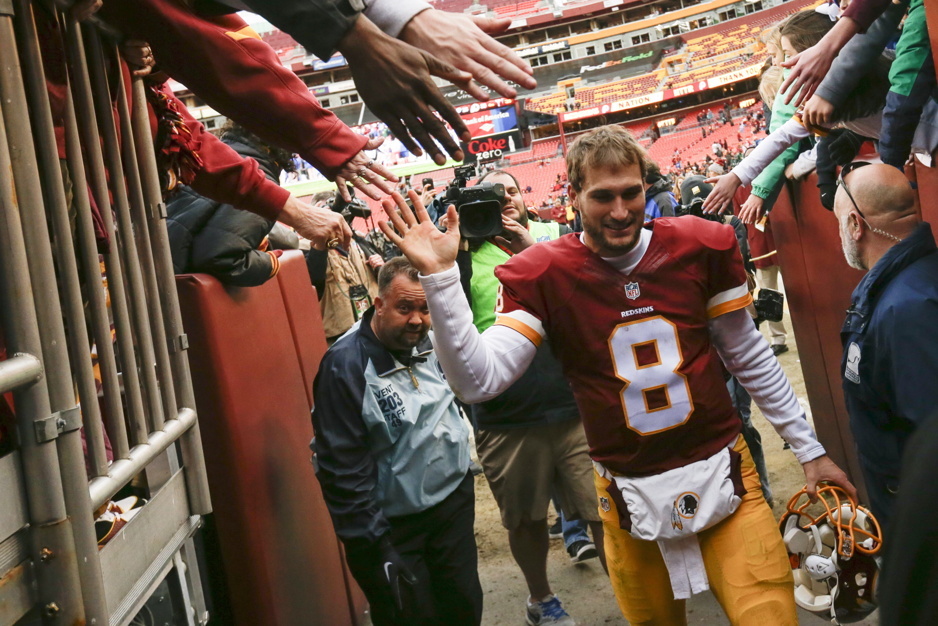 Washington Redskins quarterback Kirk Cousins (8) is greeted by fans as he leaves the field after an NFL football game against the Buffalo Bills in Landover, Md., Sunday, Dec. 20, 2015. The Washington Redskins defeated the Buffalo Bills 35-25. (AP Photo/Jacquelyn Martin)