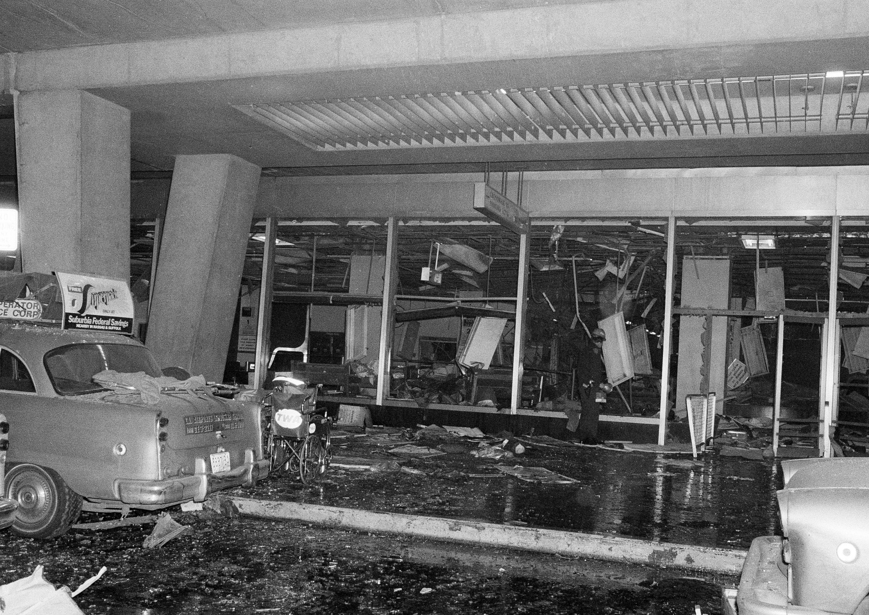 A solitary police rescue officer scans debris at New York's La Guardia Airport, Dec. 29, 1975, after a power explosion demolished a terminal baggage claim area. At least 11 persons were killed. (AP Photo)