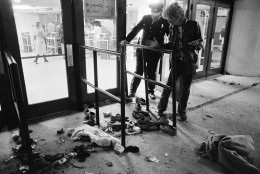 A security guard and an unidentified man look at an area where several people were killed as they were caught in a surging crowd entering Cincinnati's Riverfront Coliseum for a Who concert on Monday. Shoes and clothes were strewn around the area where the people were killed and injured, shown Dec. 4, 1979. (AP Photo/Brian Horton)