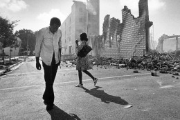 People walk past ruins in the Culmer section of Miami May 19, 1980 after rioting over the acquittal of four police officers charged with the 1979 beating death of Arthur McDuffie, a black motorcyclist. (AP Photo/Kathy Willens)