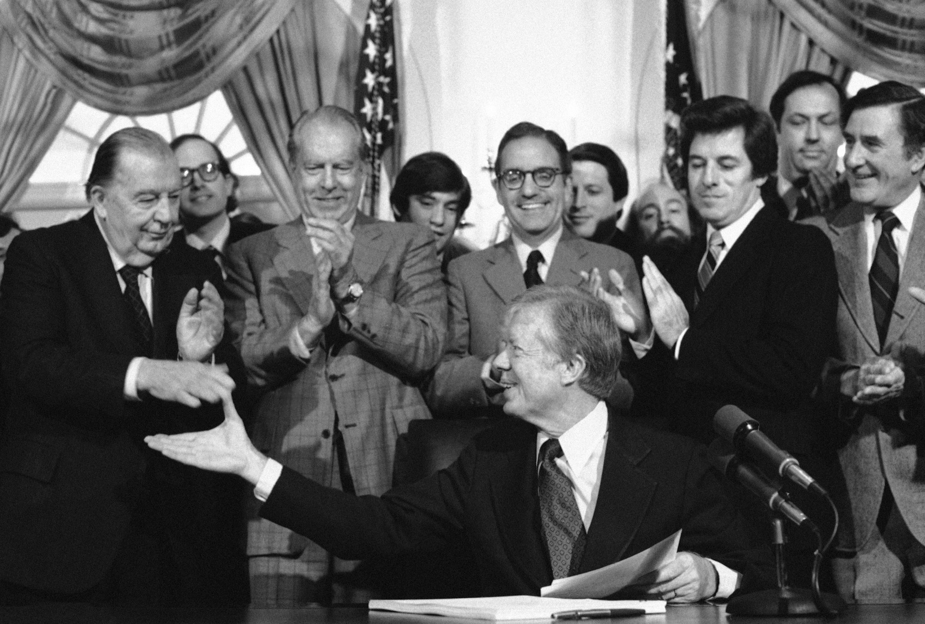 President Jimmy Carter reaches over to shake hands with Sen. Randolph Jennings, D-W.Va., left, after signing the environmental Superfund legislation in the Cabinet Room of the White House in Washington on Dec. 11, 1980. Behind Carter from left: Jennings; Sen. Robert Stafford, R-Vt., applauding; Rep. George Mitchell, D-ME., behind Carter; Rep. Al Gore, D-TN; Rep. James J. Florio, D-N.J., also applauding; Sen. Bill Bradley, D-N.J., behind Florio; and Sen. John H. Chafee, R-R.I., far right. (AP Photo/Dennis Cook)